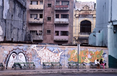 Two Girls Sitting on Bench in Front of Wall of Graffiti
